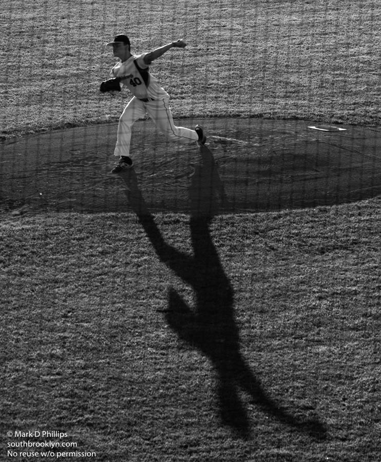 Worcester Bravehearts pitcher Shawn Babineau casts a large shadow as he pitches against the Brockton Rox at Hanover Insurance Park at Fitton Field on the campus of the College of the Holy Cross. ©Mark D Phillips