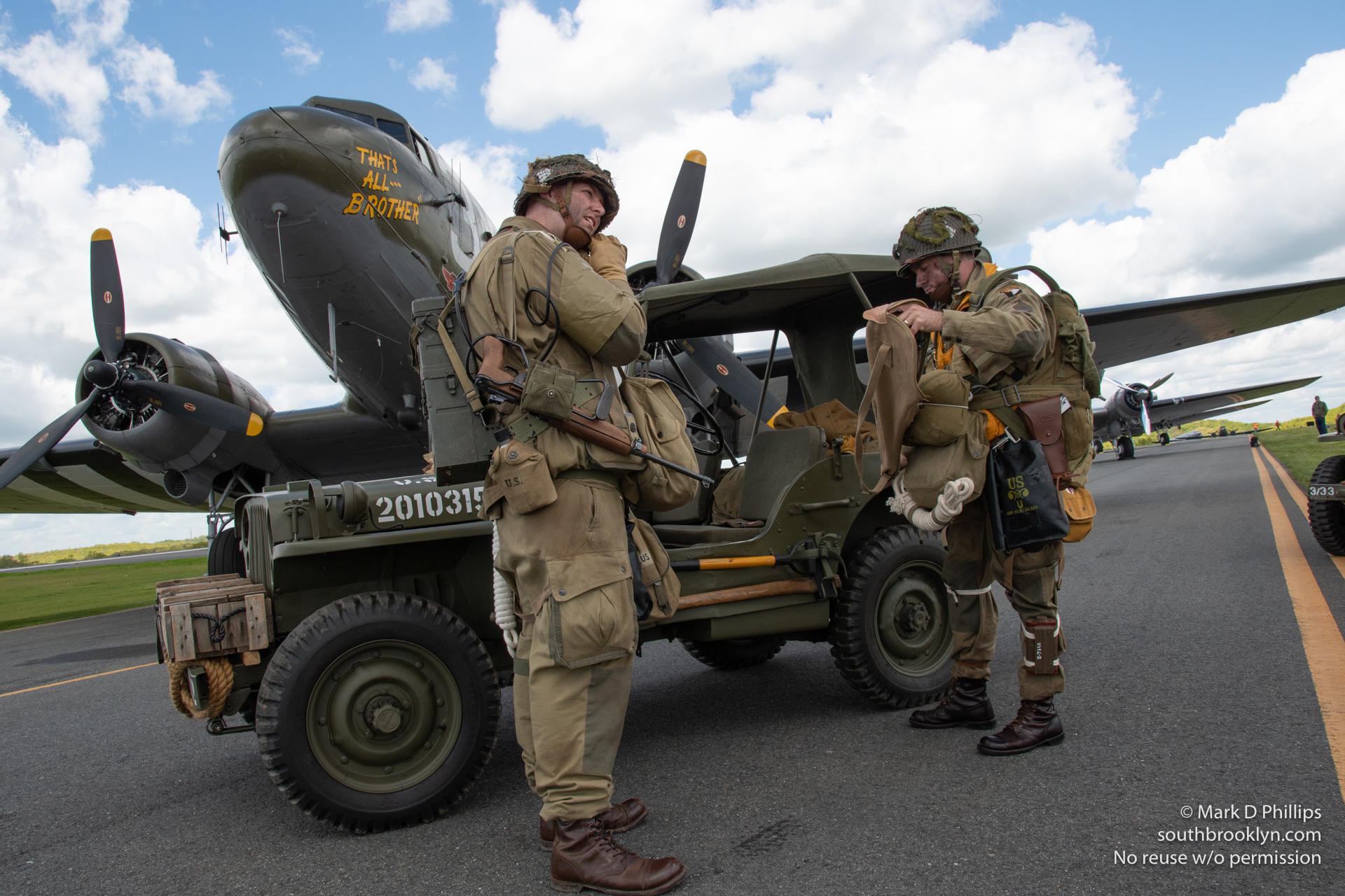 World War II reenactors, several of whom will jump from the planes over Normandy in the anniversary celebration, completed the transformation as they drove up in a jeep with all their gear to begin the invasion of Europe. ©Mark D Phillips
