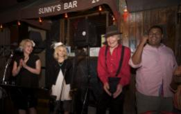 Sunny Balzanno (in Red) celebrates as Sunny's Bar is reopened 10 months after Hurricane Sandy